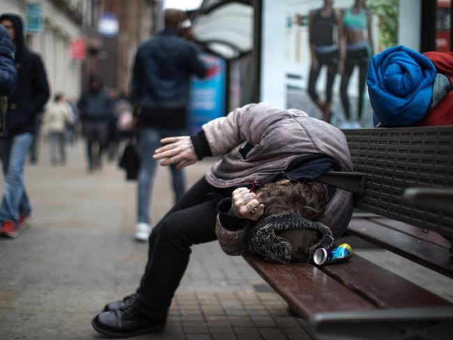 A man with a pipe in his hand lies slumped on a bench in front of a supermarket. Picture: Joel Goodman/LNP