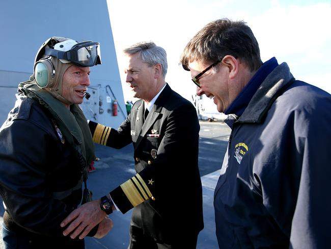 Fully equipped ... a goggled, headphoned and leather-jacket clad Mr Abbott is met by Vice Admiral Robert L Thomas and US Ambassador John Berr. Picture: Tim Hunter