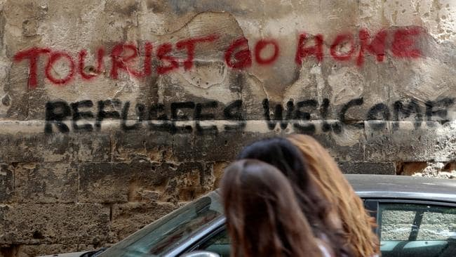 People walk past graffiti in Palma, on the Spanish island of Majorca, on May 23, 2016. Picture: Reuters/Enrique Calvo