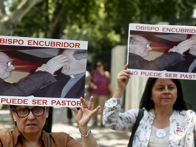 "Protesters hold up images showing the Rev. Fernando Karadima and bishop Juan Barros reading ""A bishop who covers up cannot be a priest"". Picture: AP"