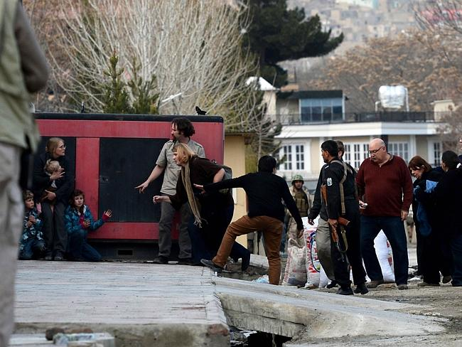 Under fire ... foreigners are escorted by Afghan police after they were evacuated from the guesthouse.