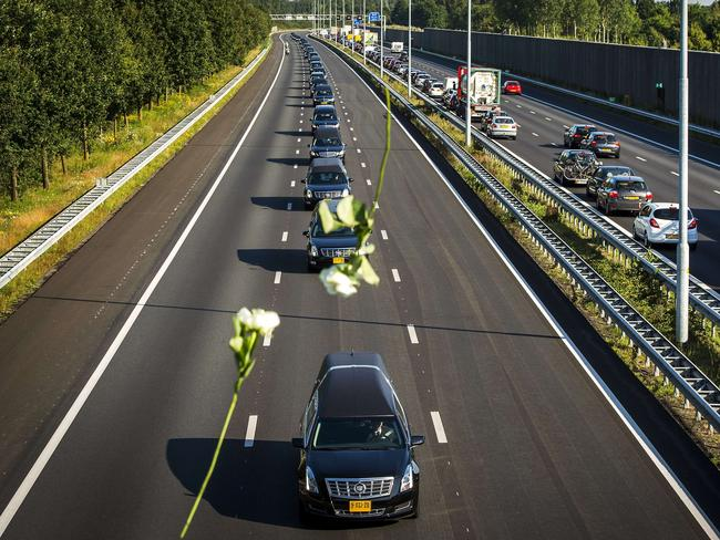 Flowers are dropped onto the hearses of the victims of MH17 from onlookers paying their respects. Picture: Remko De Waal