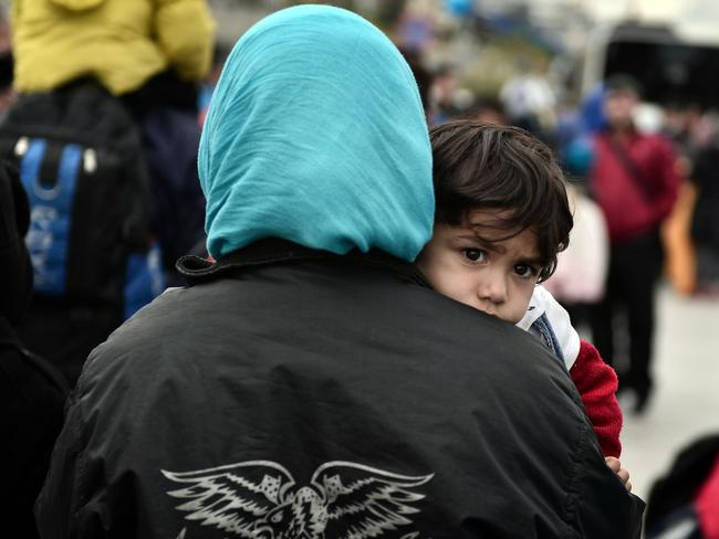 Humanitarian crisis ... a migrant carrying her child, disembarks, with other refugees and migrants, from a government chartered ferry, at the port of Piraeus in Greece.