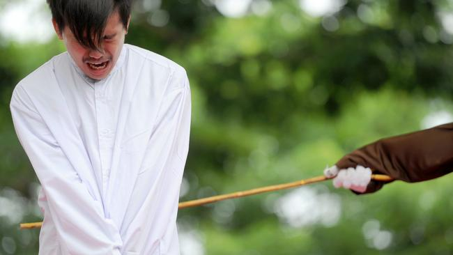 One of two Indonesian men is publicly caned for having sex, in a first for the Muslim-majority country where there are concerns about growing hostility towards the small gay community. Picture: AFP/ Chaideer Mahyuddin