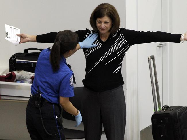 A woman undergoes a pat-down during TSA security screening.