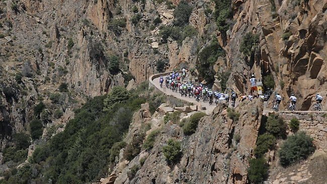 The pack speeds downhill passing the Red Rocks near Piana during the third stage of the Tour de France cycling race over 145.5 kilometers (91 miles) with start in Ajaccio and finish in Calvi, Corsica island, France, Monday July 1, 2013. (AP Photo/Laurent Cipriani)