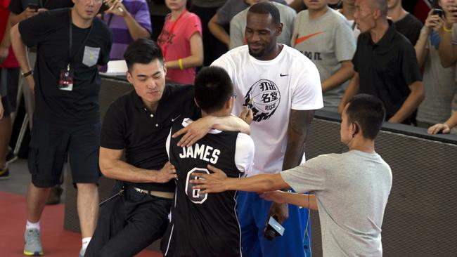 Security personnel tackle a Chinese fan who hugged NBA basketball star LeBron James.