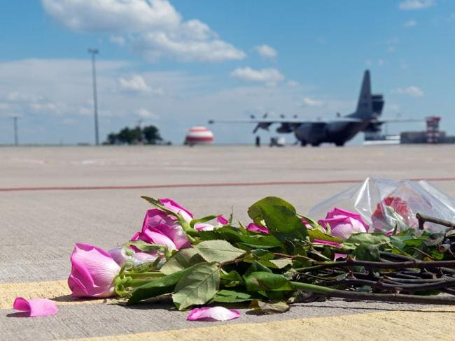 Respect ... Flowers lay on the tarmac as a Hercules transport aircraft of the Royal Dutch Airforce, carrying bodies from downed Malaysia Airlines flight MH17, prepares to take off from Kharkiv airport yesterday.