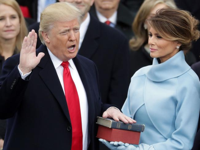 Donald Trump takes the oath of office as his wife Melania Trump holds the bible on the West Front of the US Capitol on January 20.