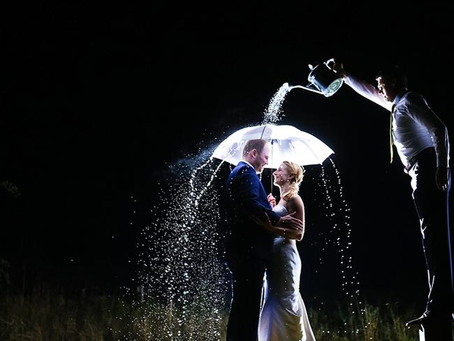 Most brides have nightmares about rain on their wedding day. Not this one... nothing like a little bit of artificial rain for that perfect photo. Picture: DENNIS JAGUSIAK / ISPWP / CATERS NEWS