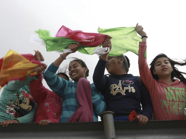 "Young people wave coloured flags reading ""Peace"" as they form a symbolic human wall along the Rio Grande, which marks the border between Mexico and the U.S. in Ciudad Juarez. Picture: AP"