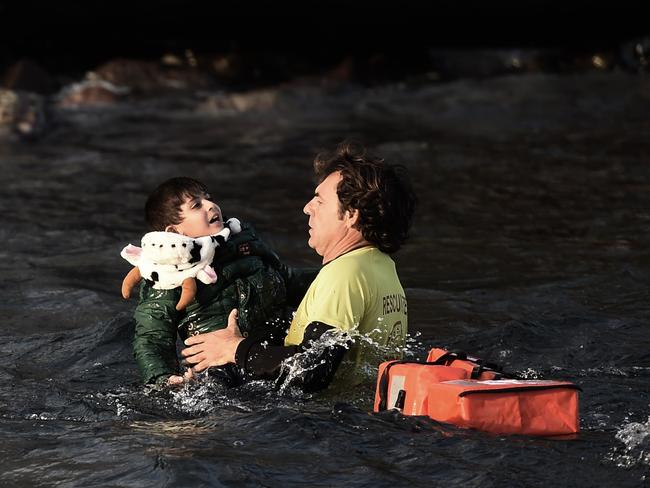 Saved from death ... Spanish lifeguard saves a migrant child as the boat he had boarded with other migrants and refugees sinks off the Greek island of Lesbos after crossing the Aegean Sea from Turkey.