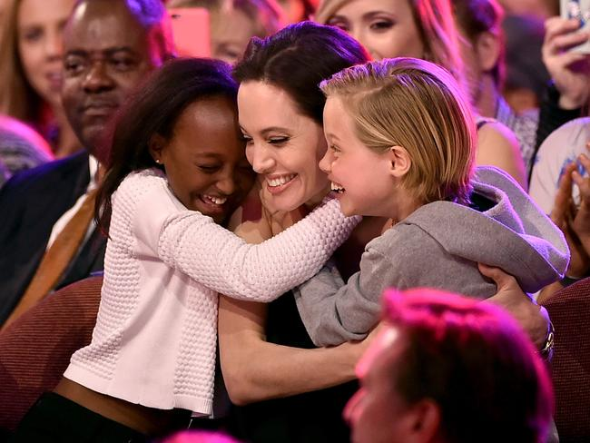 Angelina Jolie hugs daughters Zahara and Shiloh after winning the Favourite Villain award for her role in Maleficent at Nickelodeon's 28th Annual Kids' Choice Awards in 2015. Picture: Kevin Winter/Getty Images