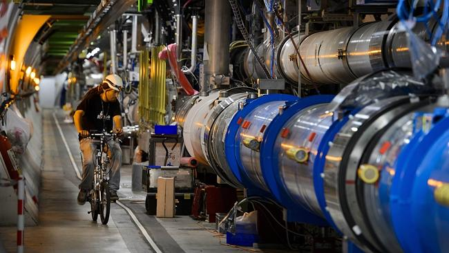 A worker rides his bicycle in a tunnel of CERN's Large Hadron Collider (LHC), during maintenance works in Meyrin, near Geneva. (Photo: AFP PHOTO / FABRICE COFFRINI)
