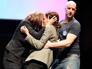 Security confront protesters who kiss on stage after they gatecrashed a Coalition for Marriage campaign launch in Melbourne, Saturday September 23 2017. (AAP Image/Joe Castro) NO ARCHIVING