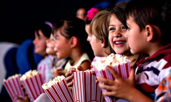 Happy group of kids at the cinema eating popcorn