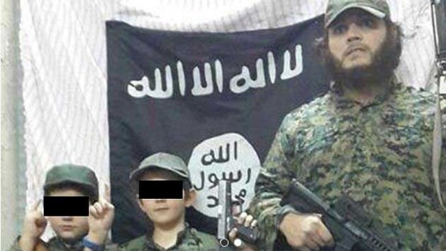 Australians ... Khaled Sharrouf and boys, believed to be his sons, stand in front of the Islamic State flag. Picture; Twitter