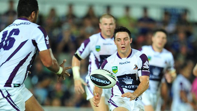 Storm star Cooper Cronk offloads a pass in his side's big win over the Cowboys at 1300SMILES Stadium.
