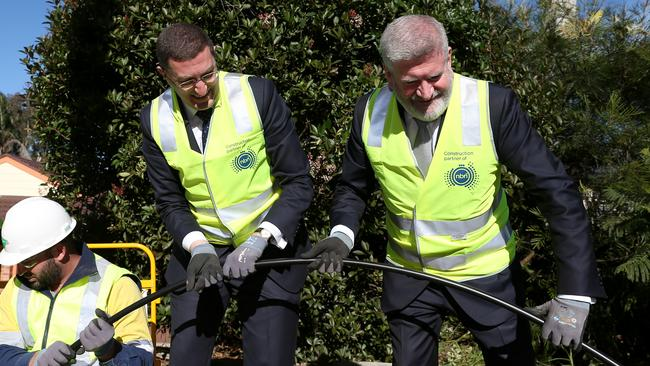Federal Minister for Communications and Arts, Senator Mitch Fifield (r) installs NBN cable with Berowra federal Liberal MP Julian Leeser. Picture: AAP Image/Ashley Feder