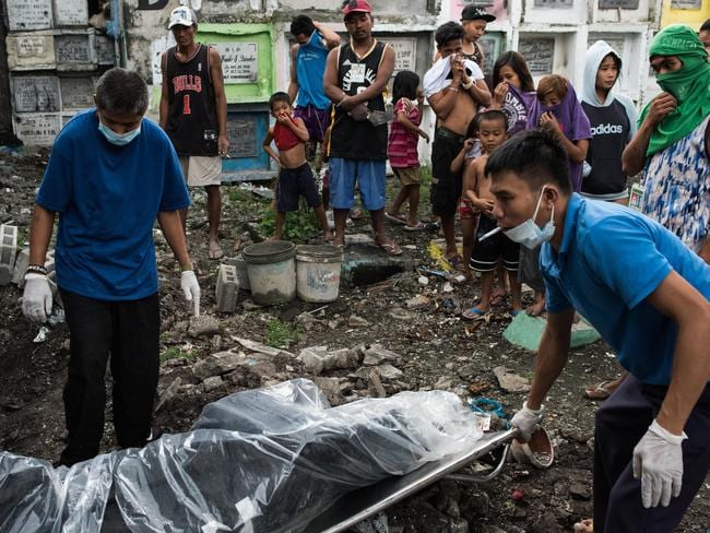 Morgue workers carry an unclaimed body and victim of an extrajudicial killing on January 24. Picture: Dondi Tawatao/Getty Images