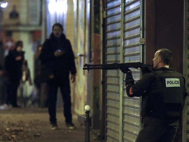 Tense situation ... A French police officer took cover while on the lookout for the shooters who attacked the restaurant 'Le Petit Cambodge' earlier in Paris. Picture: EPA/ETIENNE LAURENT