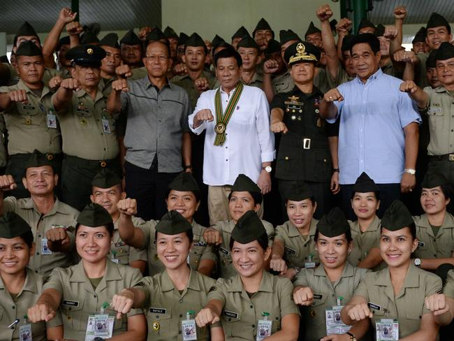 "Philippine President Rodrigo Duterte (C) along with Defence Secretary Delfin Lorenzana (centre L) and Army chief Eduardo Ano (centre R) gesture for a photo session during a ""talk to the troops"" visit to meet military personnel in Manila. Picture: AFP"