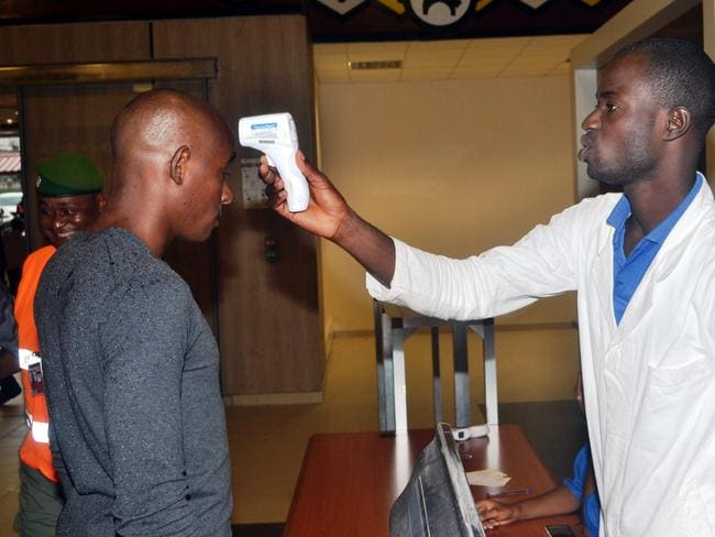 Health care ... An agent checks a passenger leaving at Conakry's airport Protection and healthcare material are being set up at African airports to fight against the spreading of the Ebola virus.