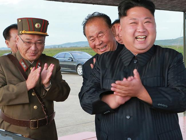North Korean leader Kim Jong-un, centre, celebrates what was said to be the test launch of an intermediate range Hwasong-12 missile at an undisclosed location in North Korea. Picture: AP