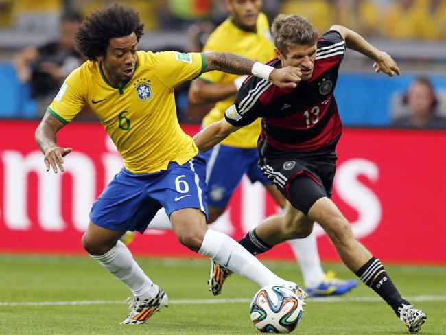 Brazil's Marcelo and Germany's Thomas Mueller challenge for the ball during the World Cup semi-final. Picture: AP Photo/Frank Augstein