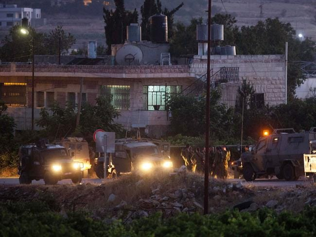 Grisly find ... Israeli soldiers stand next to their vehicles in the village of Halhul, near the West Bank town of Hebron, where the bodies of the three missing Israeli teenagers were found.