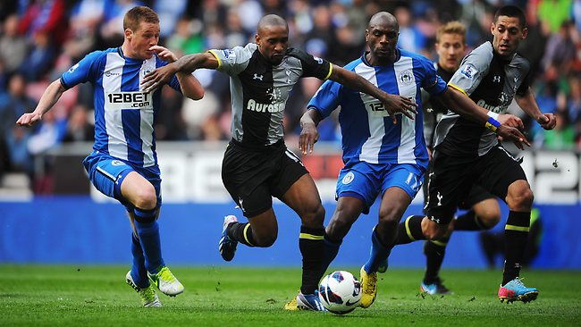 Jermain Defoe (C) of Tottenham Hotspur holds off the challenge of James McCarthy (L) and Emmerson Boyce (R) of Wigan Athletic the DW Stadium. Picture: Michael Regan