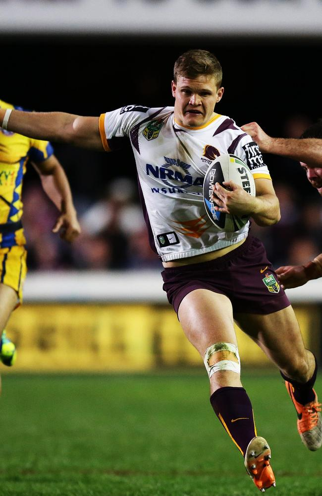 Brisbane's Dale Copley attempts to break a tackle by Manly's Josh Starling.