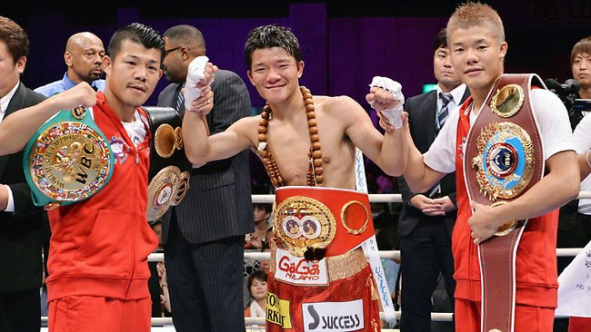 Japan's Daiki Kameda (C) poses with his elder brother Koki (L) and younger brother Tomoki (R) after he defeated Rodrigo Guerrero of Mexico at the IBF super-flyweight title boxing match in Takamatsu.