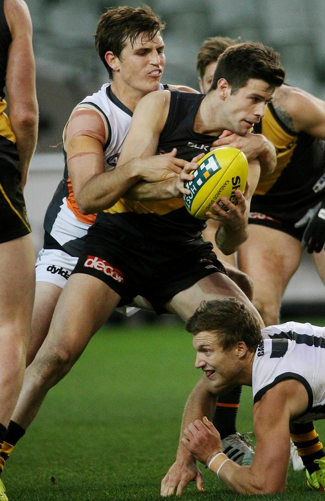 Trent Cotchin is tackled by Phil Davis and Rhys Palmer. Picture: Colleen Petch