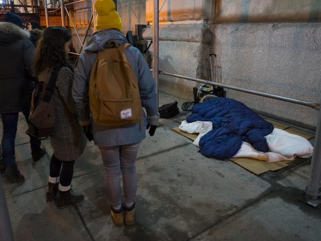 A sleeping homeless person seeks shelter under a sleeping bag in Manhattan.