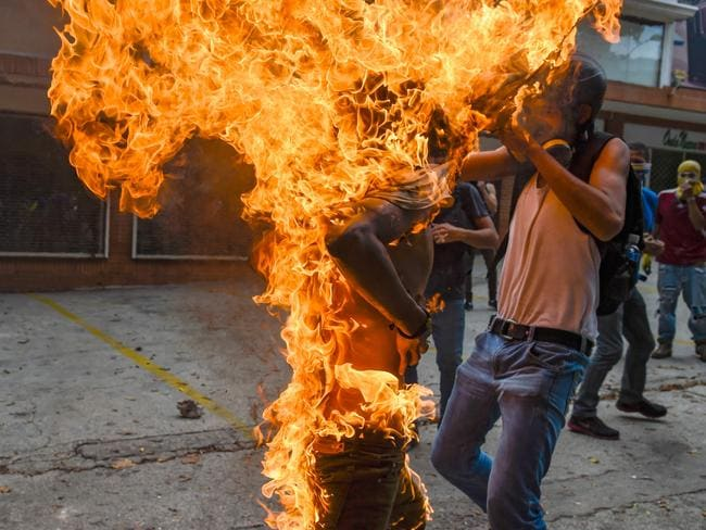 A man tries to help a fellow demonstrator who catches fire, after the gas tank of a police motorbike exploded in Caracas. Picture: Juan Barreto.