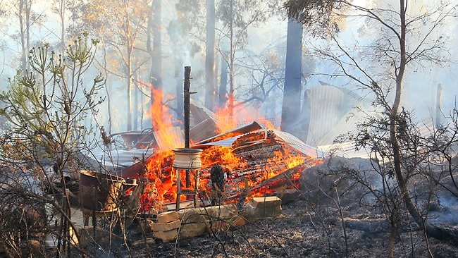 The smouldering ruins of a house/shanty destroyed by bushfire in Glen Huon. Picture: Luke Bowden
