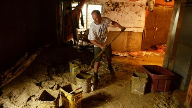 Mike Steinpach moves mud out from the basement of Stan McDonald's house, damaged by flooding. Photo: AP