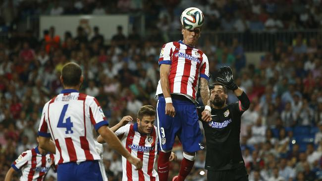 Atletico's Mandzukic top, jumps for the ball in between players during a Spanish Supercup first leg.