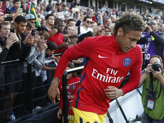 Supporters cheer PSG's Neymar as he arrives on the pitch.