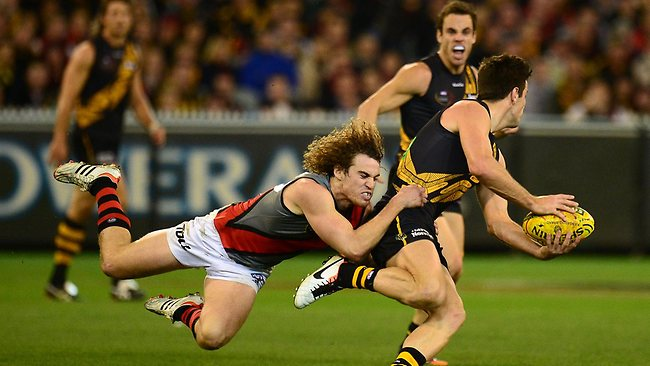 Richmond captain Trent Cotchin is run down by Essendon utility Nick Kommer. Picture: Wayne Ludbey