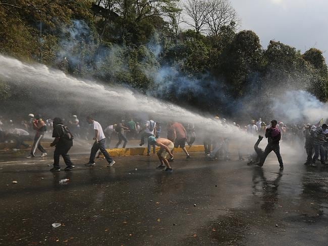 Demonstrators take cover ... from the water cannon during clashes. Picture: AP/Fernando Llano