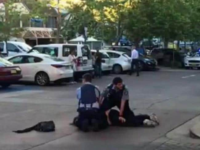 Police pin down the accused woman in a Neutral Bay carpark. Picture: Seven News