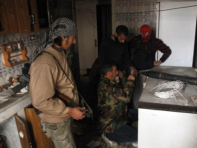 Opposition fighters prepare a homemade rocket in a kitchen of an abandoned house during clashes with government forces in the northern Syrian city of Aleppo on January 12, 2014.