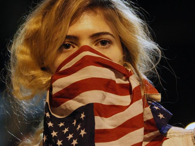 This poignant image shows a woman protesting police violence, cloaked in an American flag.