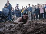 A man dives into a makeshift mud pit at the 2017 Deni Ute Muster on September 30, 2017 in Deniliquin, Australia. The annual Deniliquin Ute Muster is the largest ute muster in Australia, attracting more than 18,000 people to the rural town of Deniliquin together to celebrate all things Australian and the icon of the Ute in a weekend of music, competitions and camping. (Photo by Brook Mitchell/Getty Images)