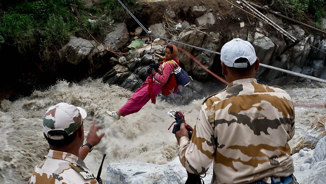 A stranded Indian pilgrim is transported across a river using a rope rescue system by Indo-Tibetan Border Police (ITBP) personnel in Govind Ghat. Up to 1000 people are feared to have died in landslides and flash floods that have left pilgrims and tourists stranded without food or water. Picture: AFP