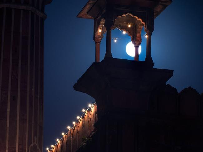 A full moon shines behind a tower of the Jama Masjid mosque in New Delhi. Picture: AFP / Roberto Schmidt