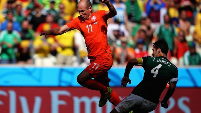 Arjen Robben of the Netherlands skips a tackle from Rafael Marquez of Mexico.