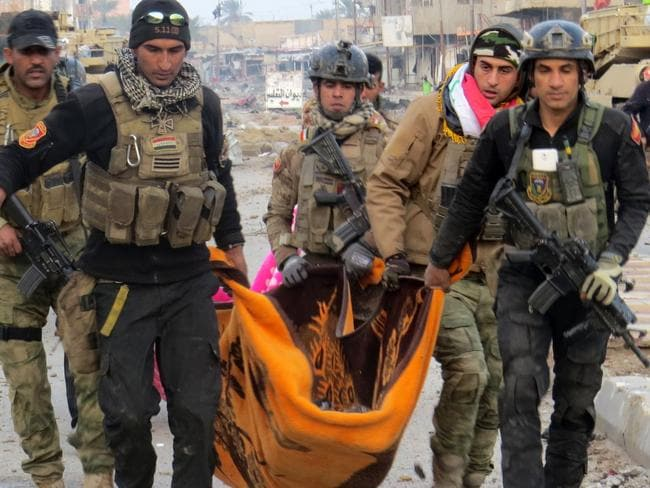 Counting cost ... Iraqi government forces and members of Iraq's elite counter-terrorism service carry the body of a comrade during battles with Islamic State (IS) group jihadists. Picture: AFP